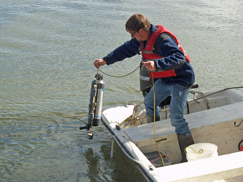 Zac Tait collects a water sample from a skiff tied to the bank.