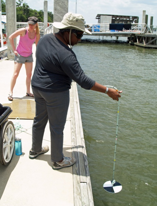 Grad student LaGina Frazier lowers a disc used to measure turbidity into the water off the UGA Skidaway Institute dock.