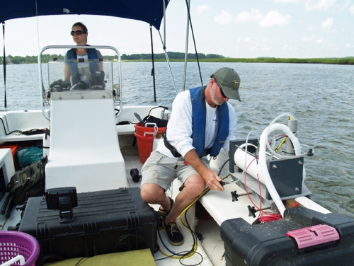 Researcher Mike Robinson prepares the adjusts the salinity sensors, while fellow researcher LeeAnn DeLeo drives the boat.
