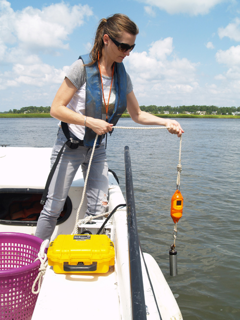 Researcher LeeAnn DeLeo lowers a CTD monitor through the water column.