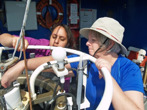 Green (left) learns to set the spring-loaded bottle plugs on a conductivity-temperature-depth sensor array with the help of Natalia Lopez Figueroa from Hampton University.