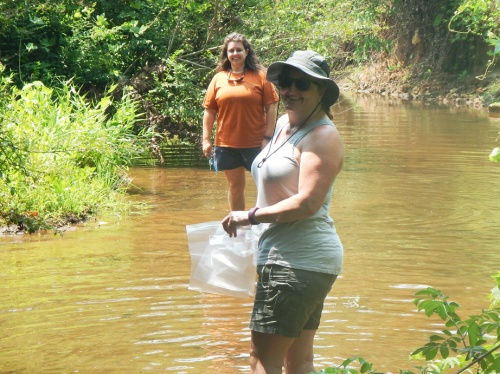 Teachers Marilyn Kinney (foreground) and Candace Bridges collect water samples in Flat Shoals Creek. Photo: Michelle Riley