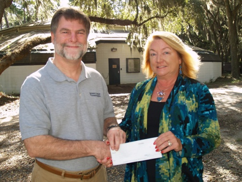 Michelle Vine presents a check to Skidaway Institute interim executive director Clark Alexander in front of the Roebling cattle barn.
